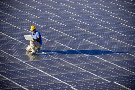 Operario sobre paneles solares en instalación fotovoltaica de energia solar
