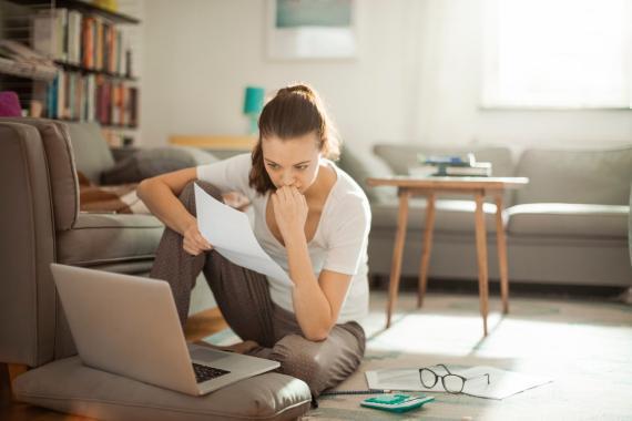 Una chica mirando una factura frente al ordenador portátil