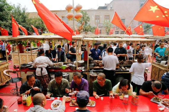 La gente come bajo las banderas nacionales chinas en la Ciudad Vieja en Kashgar