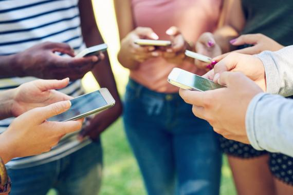 Un grupo de jóvenes utilizando teléfonos móviles