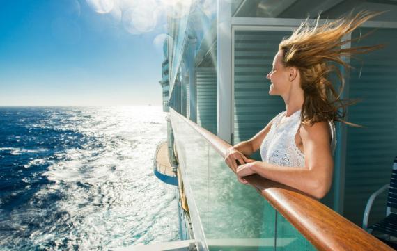 Una mujer mira al mar desde la terraza de la suite de su crucero