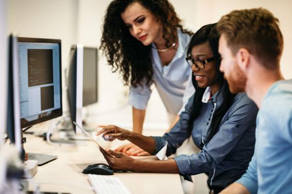 Tres trabajadores ante un ordenador.