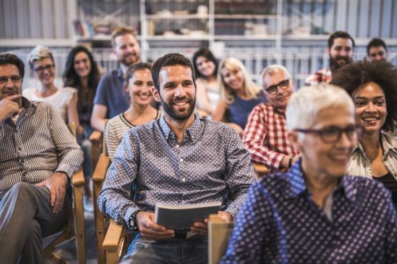 Un grupo de trabajadores sonríen en una reunión en la oficina