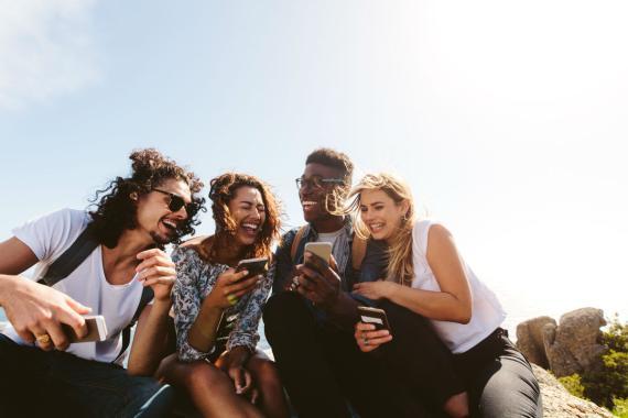 Cuatro millennials se ríen mientras se relacionan con sus smartphones.