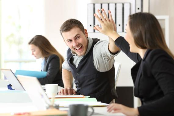 Dos empleados chocan la mano en el trabajo.