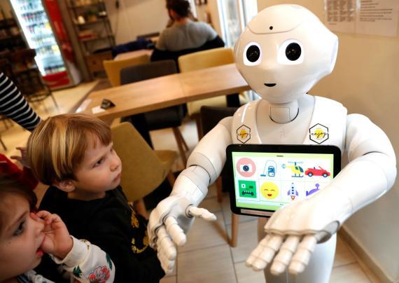 Unos niños miran a un robot con dibujos.