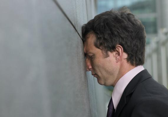 Un hombre preocupado con la cabeza contra la pared.
