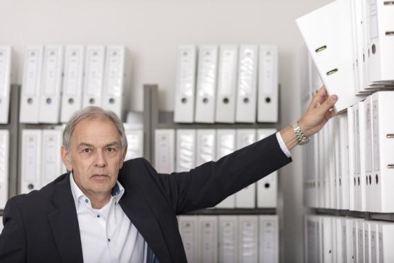 Un funcionario coloca un archivador en una estantería