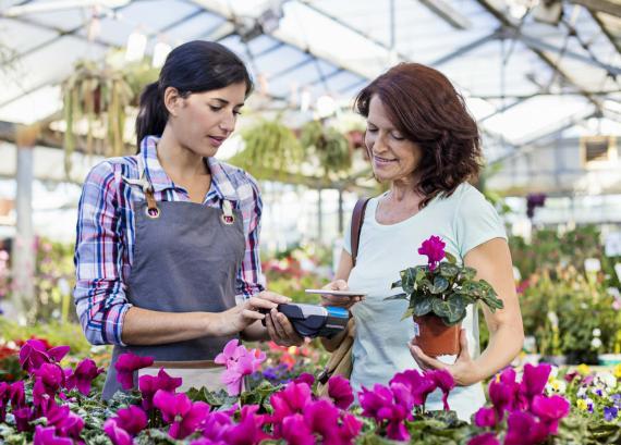 Una mujer compra una planta y paga con el móvil.
