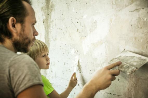 Un padre y su hijo pintan una pared agrietada