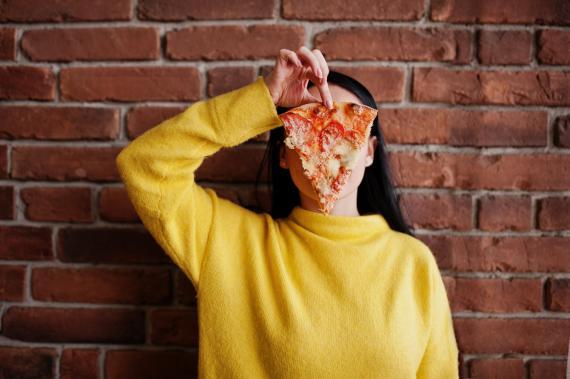 Una chica comiendo pizza