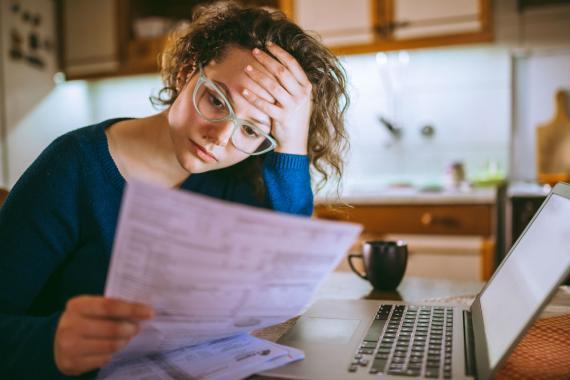 Una joven repasa documentos ante su ordenador
