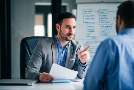 Un entrevistador habla con un candidato en una entrevista de trabajo.