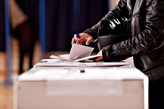 Un hombre deposita su voto en una urna.