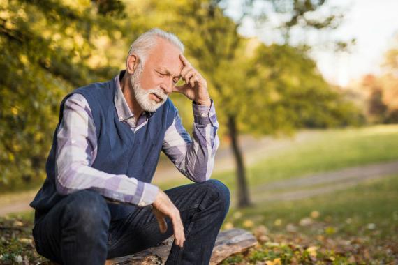 Un hombre reflexiona en un parque.