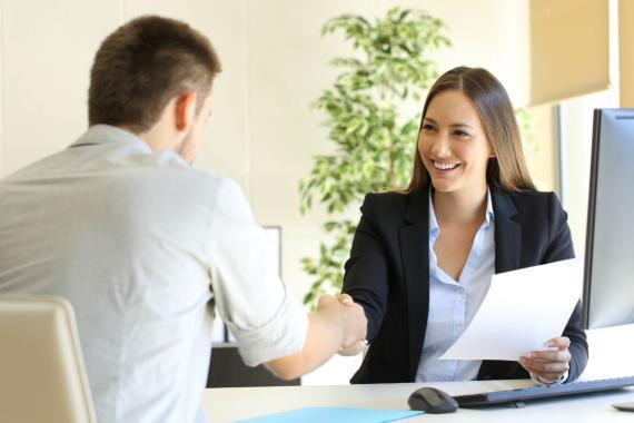 Una mujer felicita a un candidato en una entrevista de trabajo.