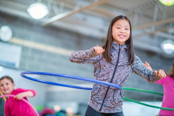 Una niña juega con un aro Hula Hoop