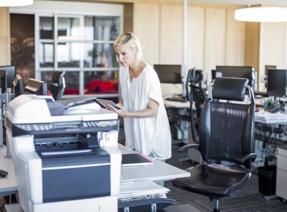 Una mujer imprime un documento en la oficina
