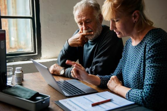 Una mujer y un hombre de mediana edad revisan documentos ante el ordenador