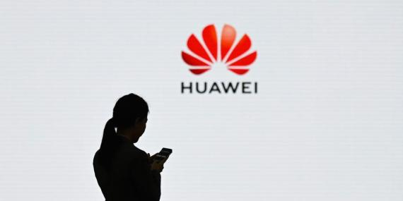 A staff member of Huawei uses her mobile phone at a conference in Shenzhen, in March 2019. The telecom company has at the center of global security concerns.