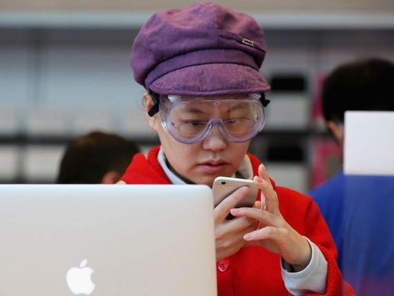 Una trabajadora maneja un iPhone en China.