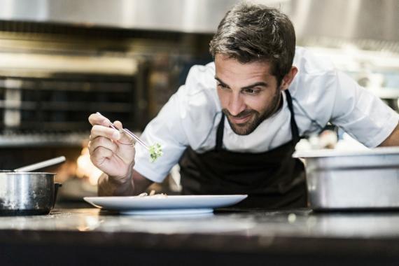 Un cocinero prepara un plato.
