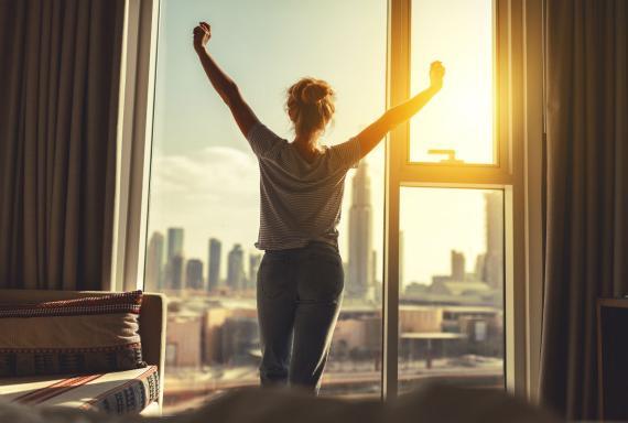 Una mujer mira por la ventana tras despertarse.