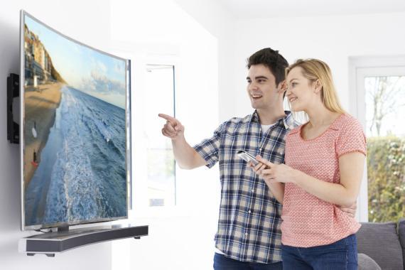 Una pareja mira un televisor 4K.
