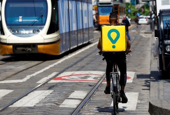 Un repartidor de Glovo en bicicleta por las calles de Milán, Italia.