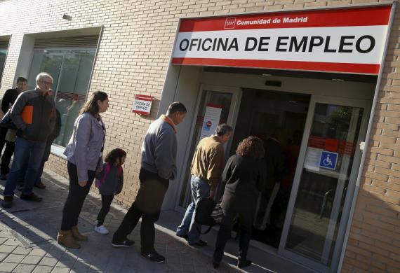 Un grupo de desempleados hace cola ante una oficina de empleo de Madrid