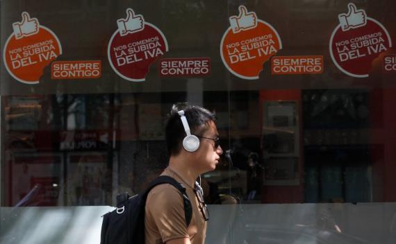 Un joven pasea ante un escaparate en el que se anuncian rebajas en el IVA