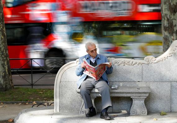 Un jubilado lee el periódico en un banco de Madrid.