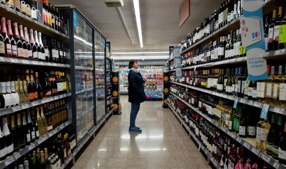 Una mujer decide qué comprar en un supermercado.