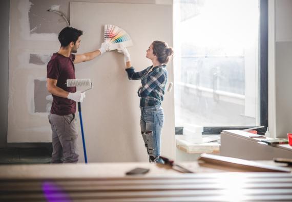 Una pareja escoge un color para pintar una pared en una reforma