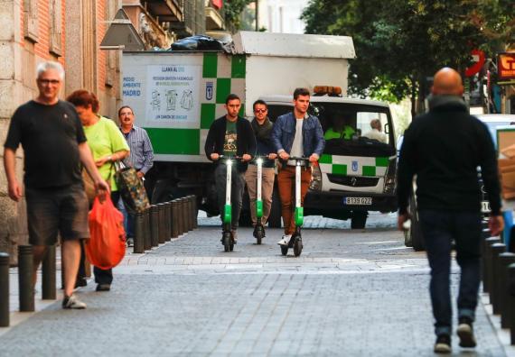 Tres jóvenes usan patinetes eléctricos compartidos de Lime en Madrid.