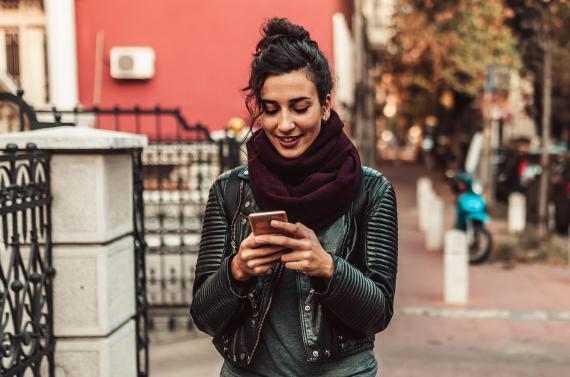 Chica usando el móvil mientras camina