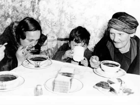 Dos mujeres y un niño desayunan en un comedor de beneficencia tras la Crisis del 29