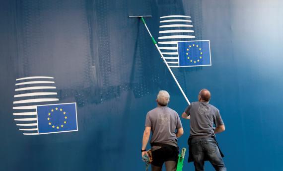 Trabajadores limpian el logo de la UE.