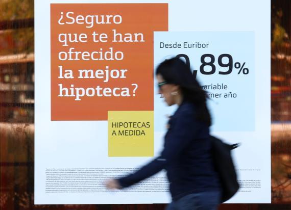 Una mujer pasa por delante de un anuncio de hipotecas en una calle de Madrid