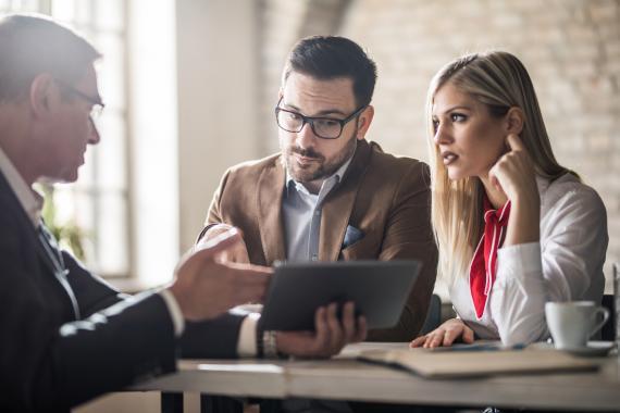 Pareja recibiendo información de un asesor financiero