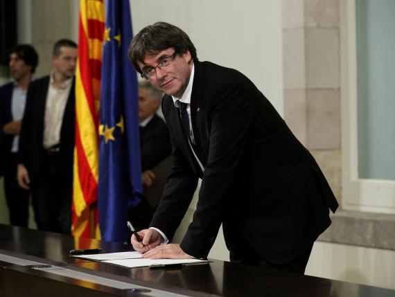 Puigdemont firma la declaración de la independencia de Cataluña en el Parlament en 2017.