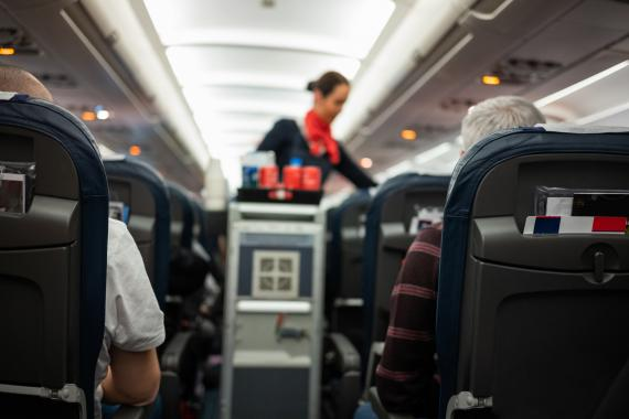 Azafata vende comida en un avión.