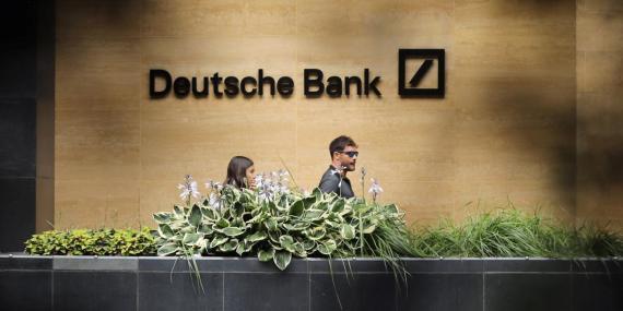 People walk past a Deutsche Bank office in London