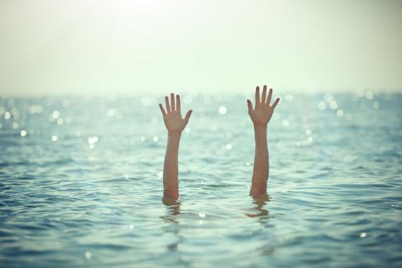 Una persona saca los brazos del mar mientras bucea