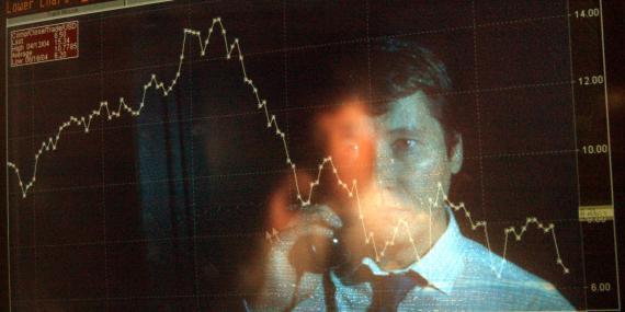 El reflejo de un trader en una pantalla en la que se ven caídas en bolsa