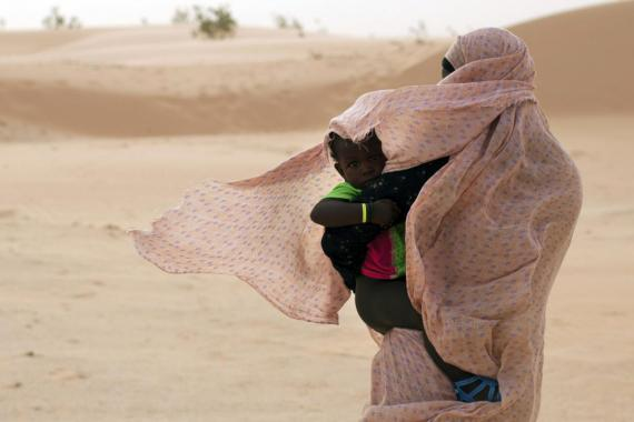 A woman shields her child from the wind while walking on sand dunes in Nouakchott, Mauritania.