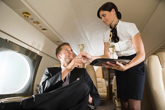 Azafata ofreciendo alcohol en el avión