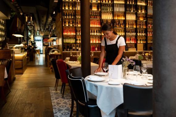 Una camarera prepara una mesa en un restaurante.