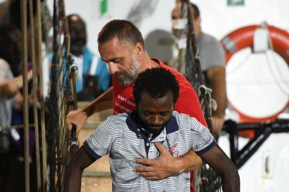 Un migrante que viajaba en el Open Arms es ayudado para desembarcar en el puerto de la isla de Lampedusa.