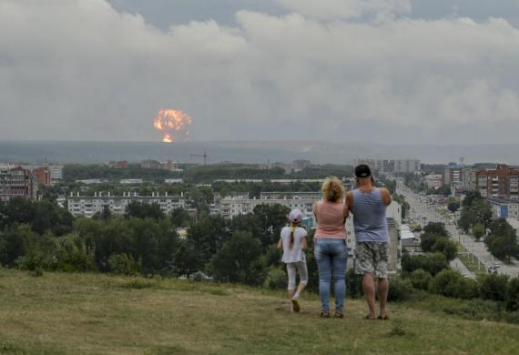 A family watches explosions at a military ammunition depot near Achinsk, Russia, on August 5, 2019.